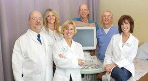 medical team in lab coats smiling at camera