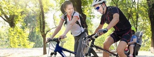 smiling couple biking next to each other